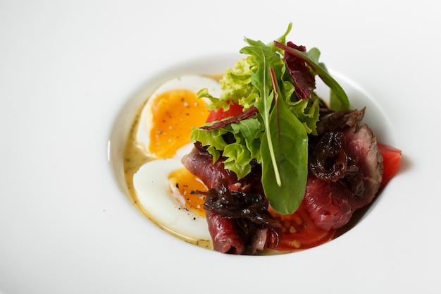 Vue de dessus de plat oeufs avec rencontrer et salade sur plaque Photo Premium