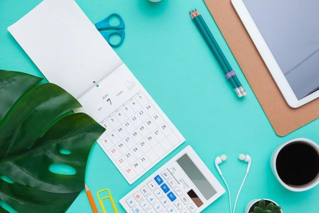 Vue de dessus plat poser de bureau espace de travail style design fournitures de bureau avec calendrier Photo Premium
