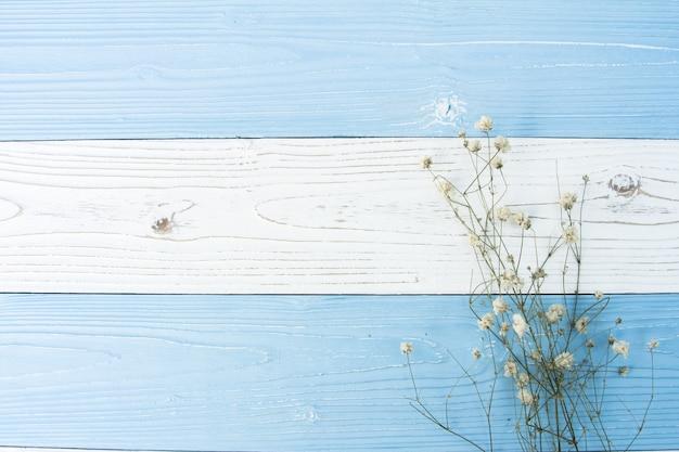Vue de dessus plat poser de fond en bois coloré décoré avec des fleurs séchées Photo Premium