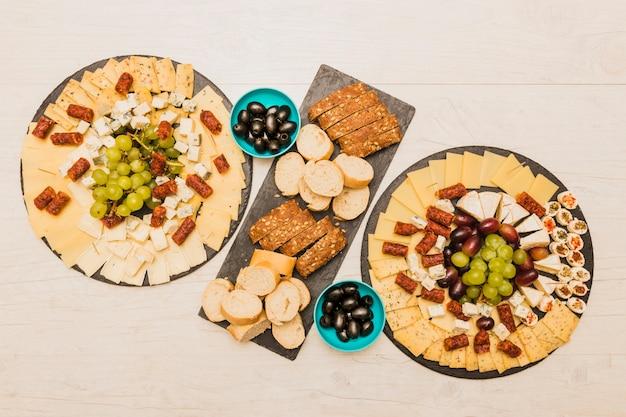 Une vue de dessus d'un plateau de fromages avec des tranches de pain et des olives sur un bureau en bois Photo gratuit