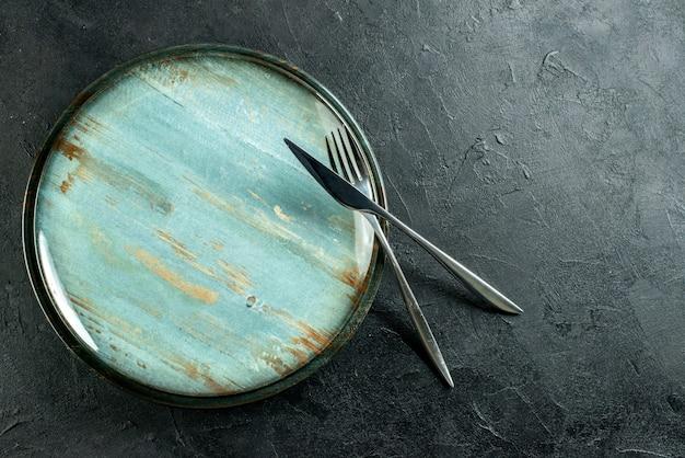Vue De Dessus Plateau Rond Fourchette En Acier Et Couteau à Dîner Sur Table Noire Avec Place Libre Photo gratuit