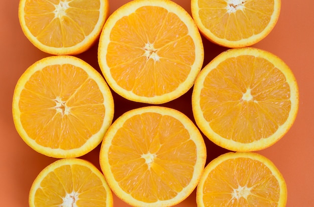 Vue de dessus de plusieurs tranches de fruits orange sur fond clair en couleur orange. une image de texture d'agrumes saturée Photo Premium