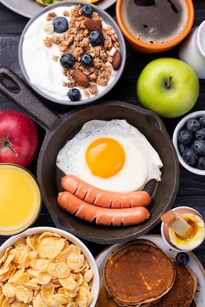 Vue De Dessus De La Poêle Avec Des œufs Et Des Saucisses Entourées De Nourriture Pour Le Petit Déjeuner Photo gratuit