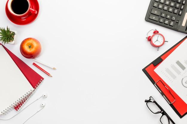 Une vue de dessus de pomme avec des papeteries sur un bureau blanc Photo gratuit