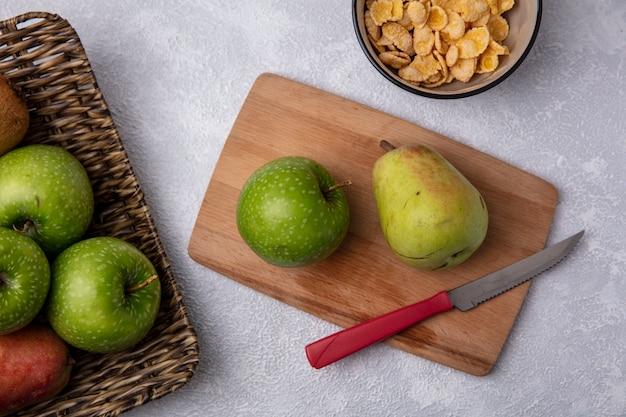 Vue De Dessus Pomme Verte Avec Poire Et Couteau Sur Planche à Découper Avec Cornflakes Dans Un Bol Sur Fond Blanc Photo gratuit