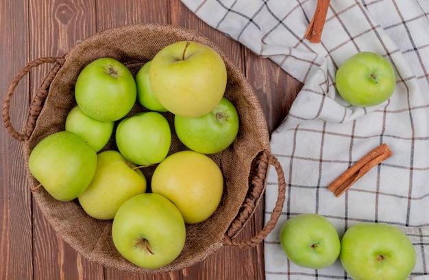 Vue De Dessus Des Pommes Vertes Et Jaunes Dans Un Panier Avec De La Cannelle Sur Un Tissu à Carreaux Et Un Fond En Bois Photo gratuit