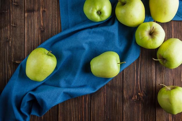 Vue De Dessus De Pommes Vertes Sur Un Tissu Bleu Et Fond En Bois Photo gratuit
