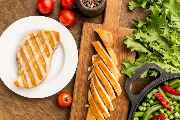 Vue De Dessus Poulet Grillé Et Tomates Avec Salade Photo gratuit