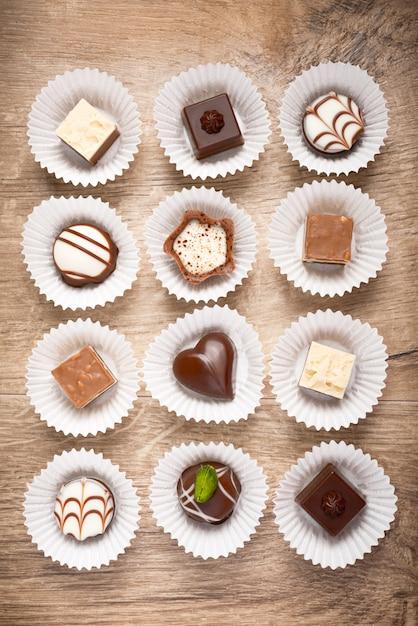 Vue de dessus sur des pralines au chocolat assorties sur bois Photo Premium