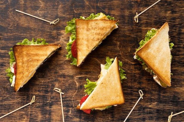 Vue De Dessus De Quatre Sandwichs Triangulaires Aux Tomates Et Salade Photo gratuit
