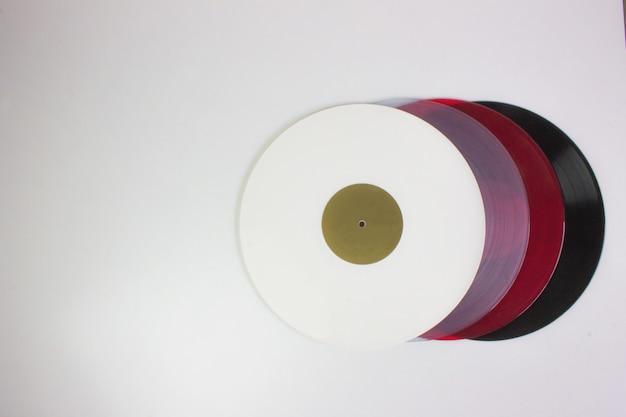 Vue de dessus de quatre vinyles, noir, rouge, bleu et blanc, sur blanc. Photo Premium