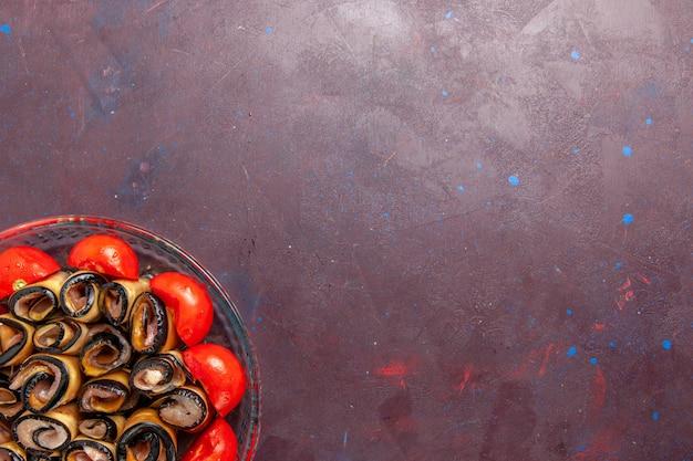 Vue De Dessus Repas De Légumes En Tranches Et Tomates Roulées Aux Aubergines Sur Le Fond Sombre Photo gratuit