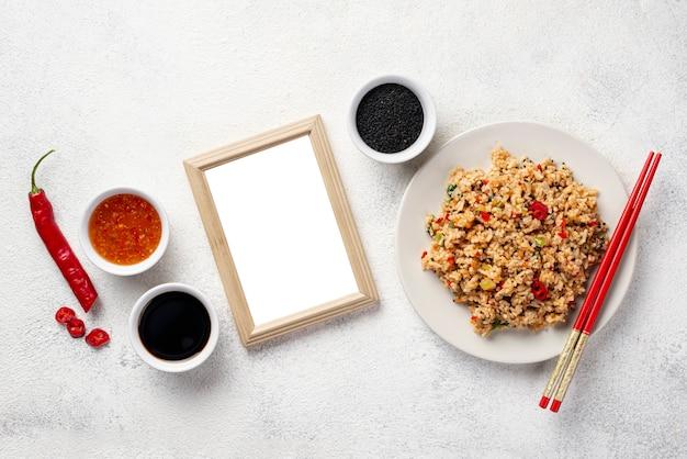 Vue de dessus, riz, à, legumes, sur, baguettes plaque, et, sauce soja, à, cadre vide Photo gratuit
