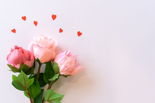 Vue De Dessus Des Roses Et En Forme De Cœur Sur Fond De Couleur Rose Pour La Saint-valentin Et Le Concept De La Fête Des Mères Photo Premium