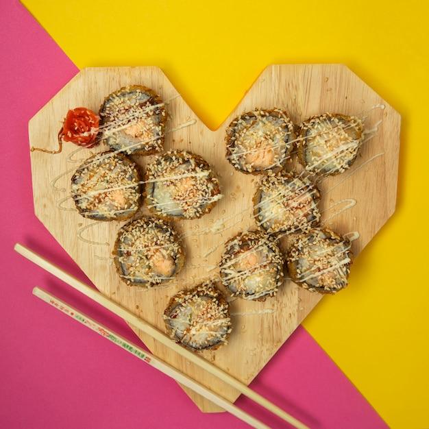 Vue de dessus des rouleaux de sushi frits en forme de coeur avec du gingembre et du wasabi Photo gratuit
