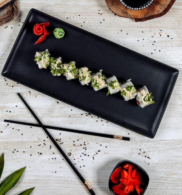 Vue de dessus des rouleaux de sushi garnie d'herbes et de fromage râpé Photo gratuit