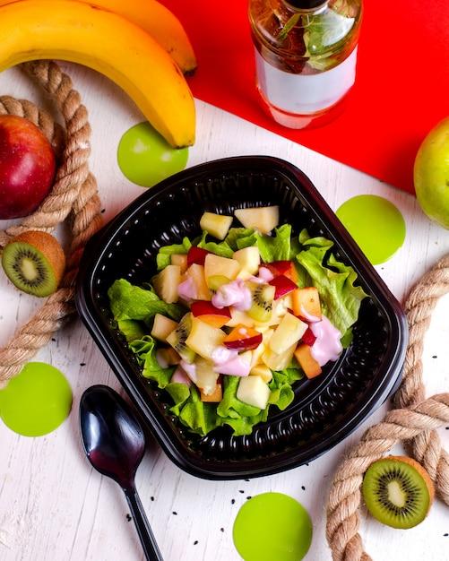 Vue De Dessus De Salade De Fruits Avec Pomme Kiwi Et Bananes Dans Une Boîte De Livraison Photo gratuit