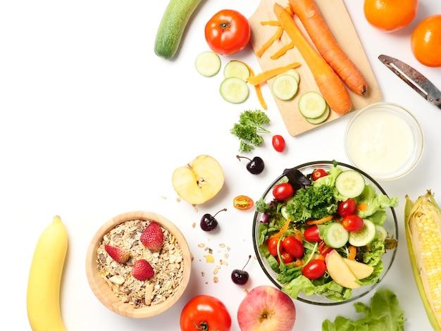 Vue de dessus de la salade de légumes mélangés, muesli et fruits frais sur fond blanc Photo Premium