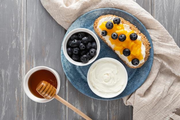 Vue De Dessus Sandwich Avec Fromage à La Crème Et Fruits Sur Assiette Avec Du Miel Photo gratuit
