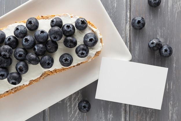 Vue De Dessus Sandwich Avec Fromage à La Crème Et Myrtilles Sur Plaque Avec Rectangle Vierge Photo gratuit