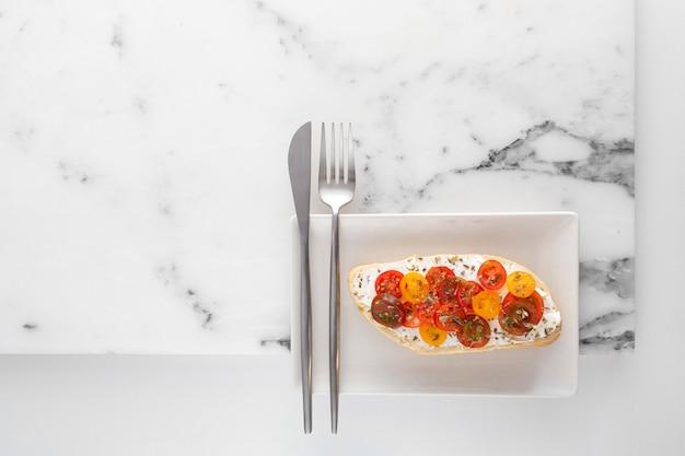 Vue De Dessus Sandwich Avec Fromage à La Crème Et Tomates Sur Assiette Avec Couverts Photo Premium