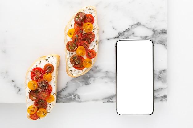 Vue De Dessus Sandwich Avec Fromage à La Crème Et Tomates Avec Téléphone Vierge Photo Premium