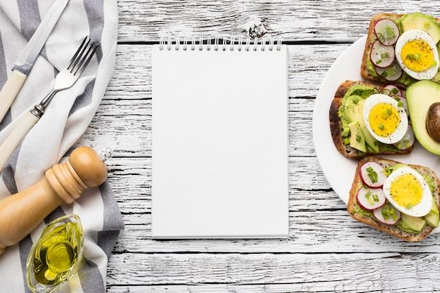 Vue De Dessus Des Sandwichs Aux œufs Et à L'avocat Sur Plaque Avec Ordinateur Portable Photo gratuit