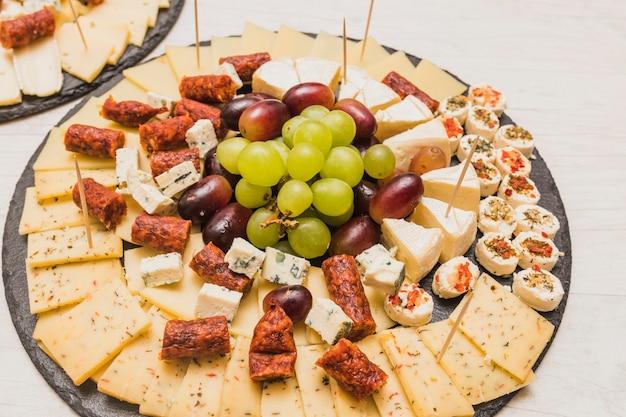 Une vue de dessus de saucisses fumées, plateau de fromages et raisins sur assiette en ardoise Photo gratuit