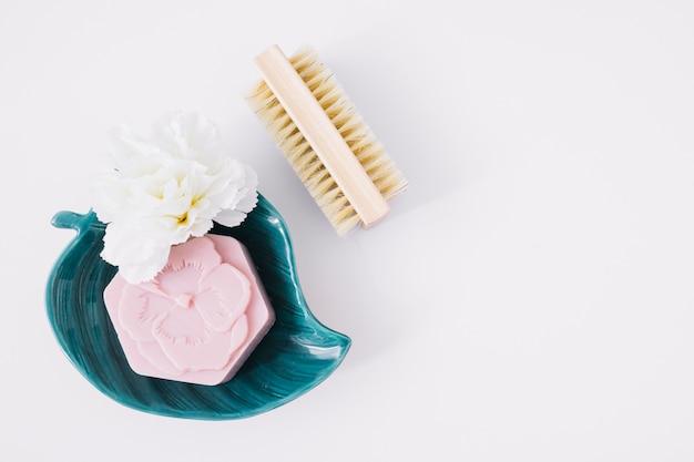 Vue de dessus de savon rose et de fleurs sur la plaque en forme de feuille près de brosse sur fond blanc Photo gratuit
