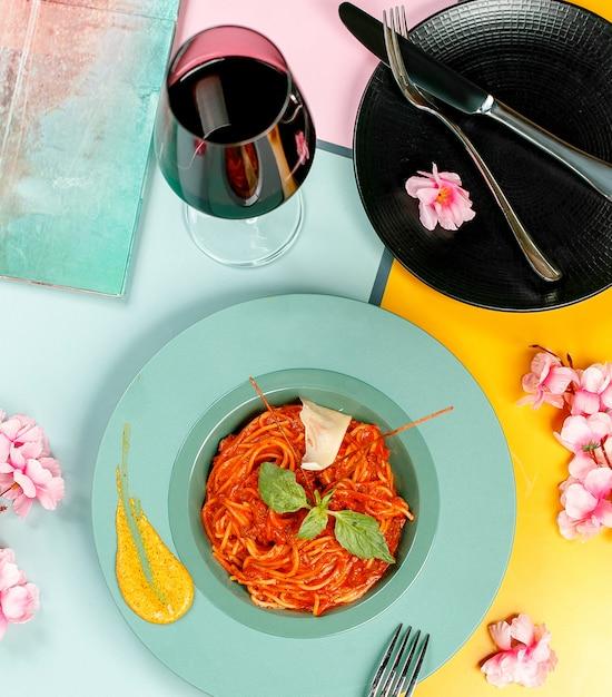 Vue De Dessus Des Spaghettis Bolognais Surmontés De Basilic Dans Une Assiette Turquoise Photo gratuit