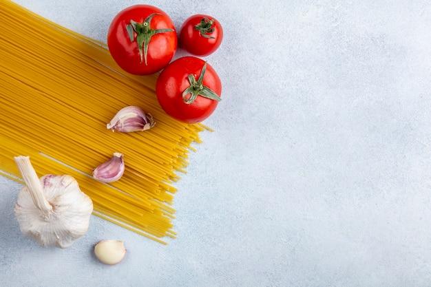 Vue De Dessus Des Spaghettis Crus à L'ail Et Tomates Sur Une Surface Grise Photo gratuit