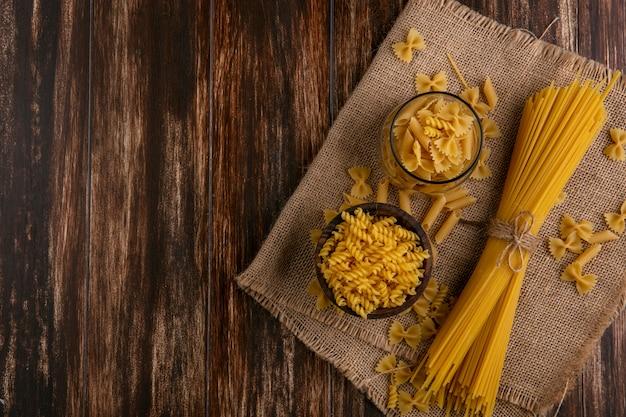 Vue De Dessus Des Spaghettis Crus Avec Des Pâtes Crues Sur Une Serviette Beige Sur Une Surface En Bois Photo gratuit