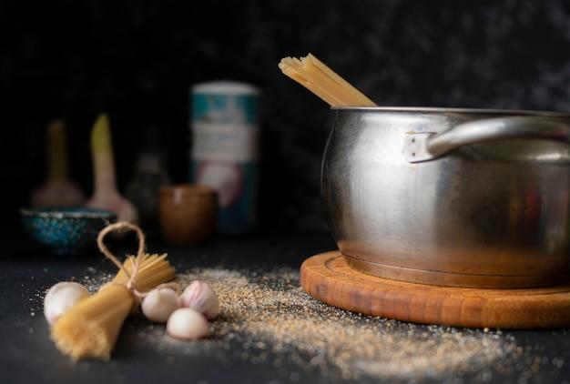 Vue de dessus de spaghettis durs crus dans une casserole en métal, eau bouillante, ingrédients pour cuisiner Photo Premium