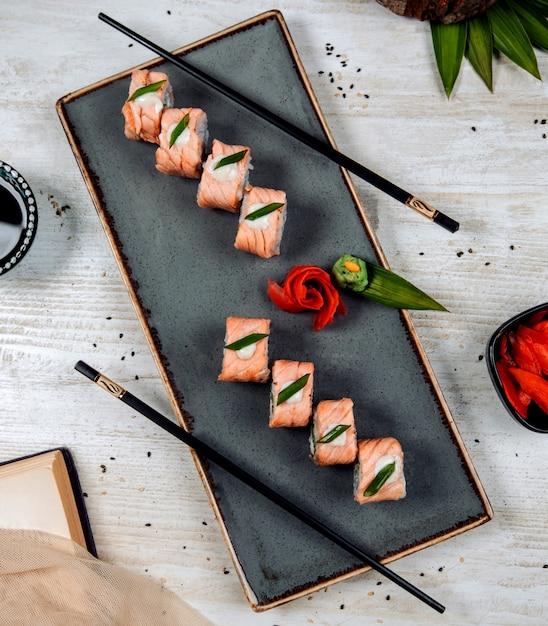 Vue de dessus des sushis au saumon garnis de tranche de crème et d'oignon Photo gratuit