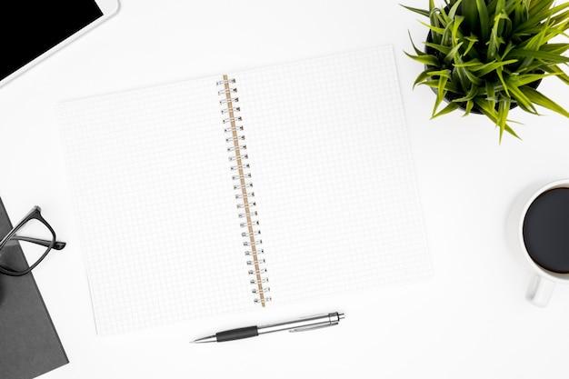 Vue de dessus de table de bureau blanc avec bloc-notes vierge avec lignes de la grille et des fournitures. Photo Premium