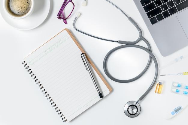 Vue de dessus de la table de bureau de médecin avec stéthoscope Photo Premium