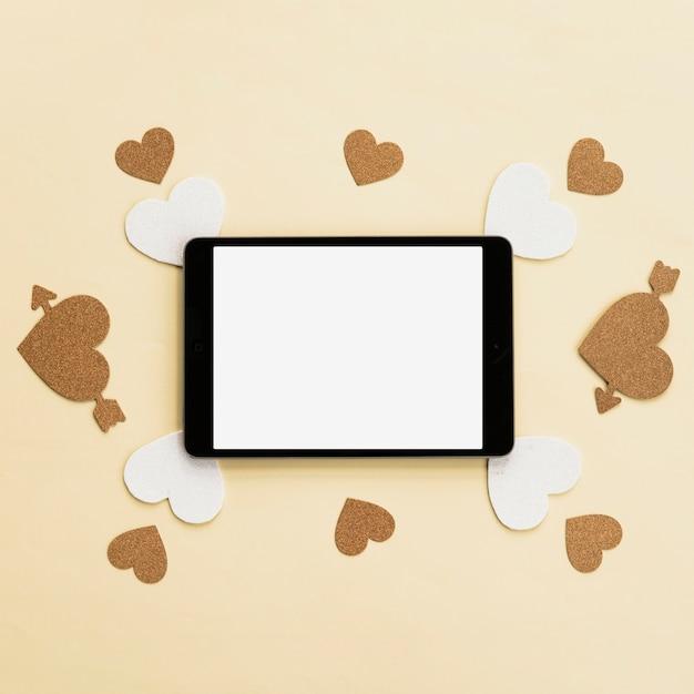 Vue de dessus de tablette numérique avec un autocollant de coeur blanc et doré sur une surface beige Photo gratuit