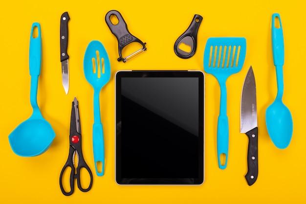 Vue de dessus de la tablette et des ustensiles de cuisine à côté de lui isolé sur jaune Photo Premium