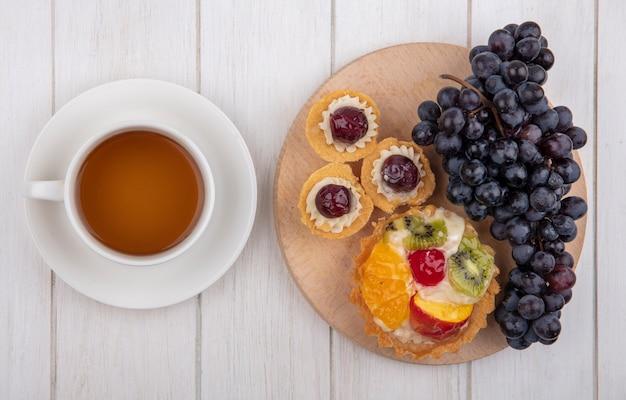 Vue De Dessus Tartelettes Aux Raisins Noirs Sur Un Support Avec Une Tasse De Thé Sur Fond Blanc Photo gratuit