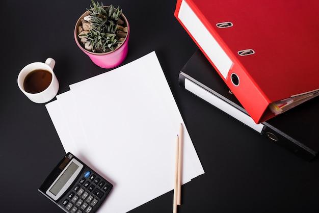 Une vue de dessus d'une tasse de café; calculatrice; plante en pot; papiers blancs vierges; crayons et fichiers papier sur fond noir Photo gratuit