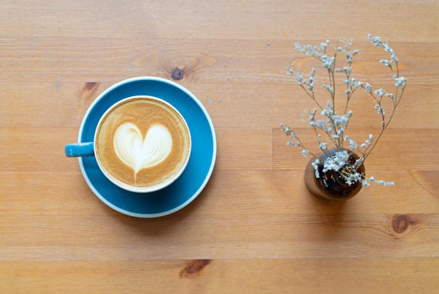Vue de dessus de la tasse de café chaud et de la fleur avec une mousse de coeur art barista sur table en bois. Photo Premium