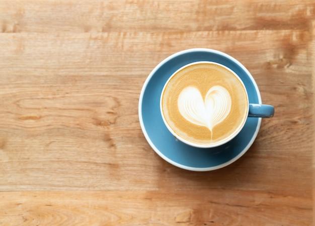Vue de dessus de la tasse de café chaud avec une mousse de forme de coeur art barista sur fond de table en bois. Photo Premium
