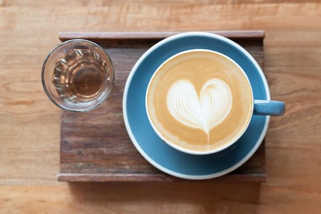 Vue de dessus de la tasse de café chaud avec une tasse de thé en mousse de forme de coeur art barista sur table en bois. Photo Premium