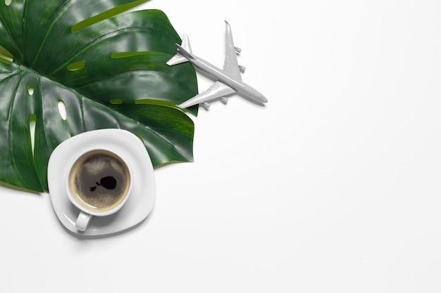 Vue de dessus tasse à café et feuille de monstera Photo Premium