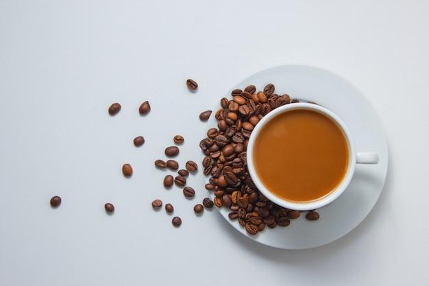 Vue De Dessus Une Tasse De Café Avec Des Grains De Café Sur Une Soucoupe Sur Fond Blanc Photo gratuit