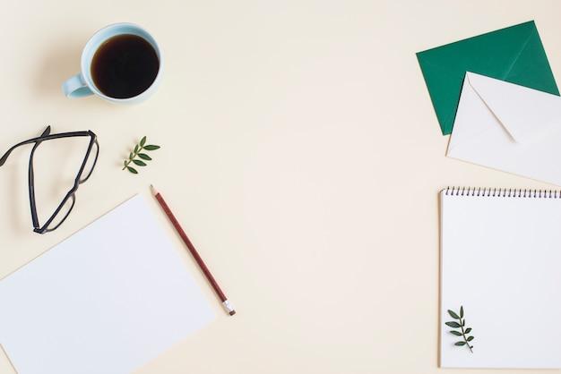 Une vue de dessus d'une tasse de café; lunettes et papeterie sur fond beige Photo gratuit
