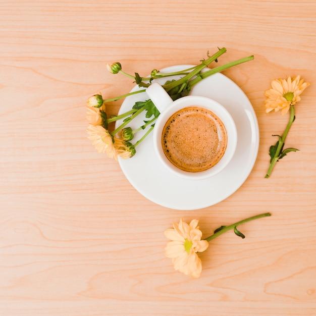Une vue de dessus de la tasse à café et une soucoupe avec des fleurs couleur pêche sur fond texturé en bois Photo gratuit