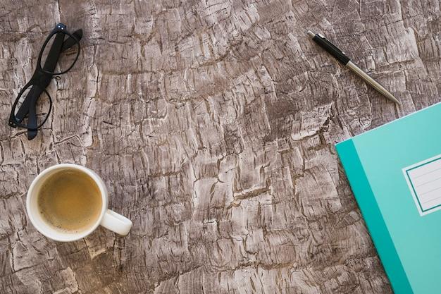 Une vue de dessus d'une tasse de café; stylo; cahier et lunettes sur fond texturé Photo gratuit