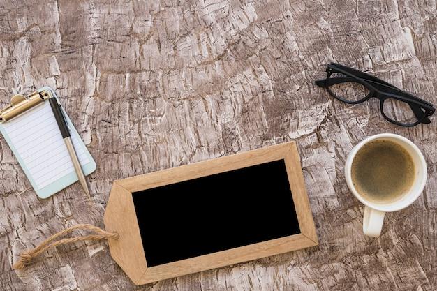 Une vue de dessus d'une tasse de café; stylo; petit presse-papiers et lunettes sur fond texturé Photo gratuit