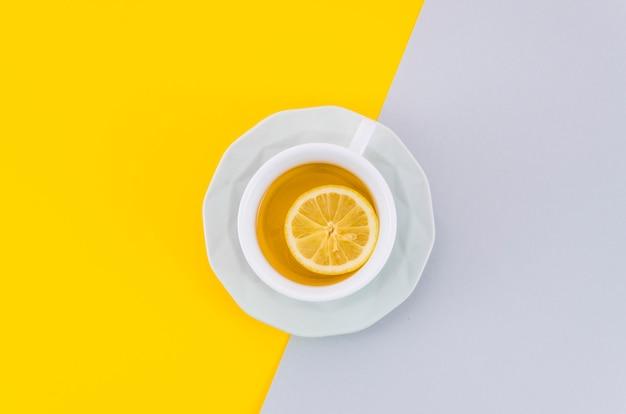 Une vue de dessus de la tasse de thé au citron et sa soucoupe sur fond blanc et jaune Photo gratuit